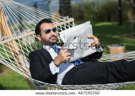 Successful businessman enjoying brake and reading newspaper on the hummock in front of cityscape of Dubai.