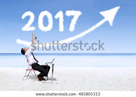 Successful businessman expressing his success at the beach under clouds shaped numbers 2017 and upward arrow