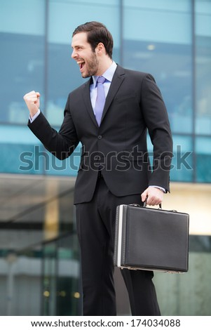 successful businessman happy after a good job in front of an office building