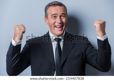 Successful businessman. Happy mature man in formalwear gesturing and smiling while standing against grey background