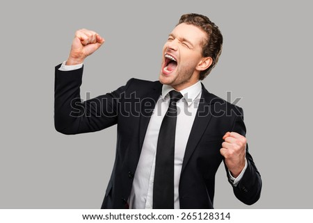 Successful businessman. Happy young man in formalwear gesturing and keeping eyes closed while standing against grey background - stock photo