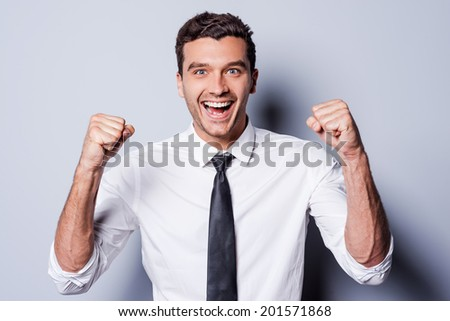 Successful businessman. Happy young man in shirt and tie gesturing and smiling while standing against grey background  - stock photo