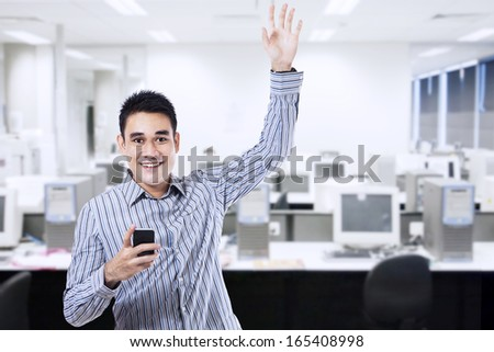 Successful businessman holding a smart phone in office - stock photo