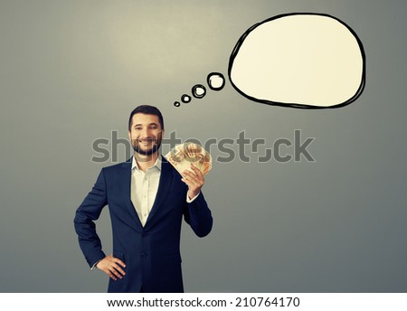 successful businessman holding paper money and smiling with drawing empty thought bubble over dark background - stock photo