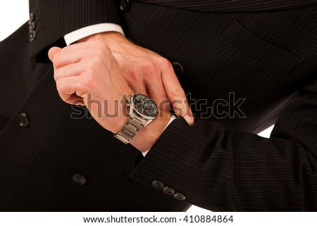 Successful businessman in formal suit checking time on wrist watch isolated over white.