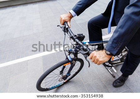 Successful businessman in suit riding bicycle  - stock photo