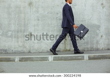 Successful businessman in suit walking along concrete wall in urban environment - stock photo