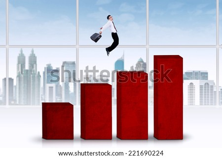 Successful businessman jumping above business chart - stock photo