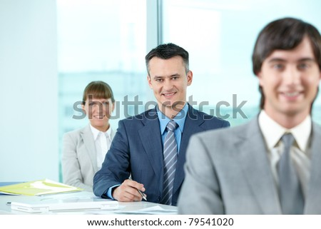 Successful businessman looking at camera between his colleagues