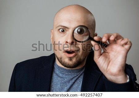 Successful businessman looking at camera through magnifier over beige background.