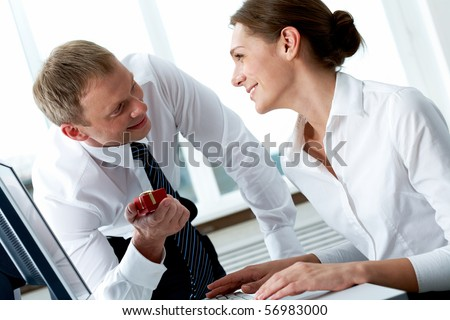 Successful businessman looking at his secretary while giving her small giftbox in office - stock photo