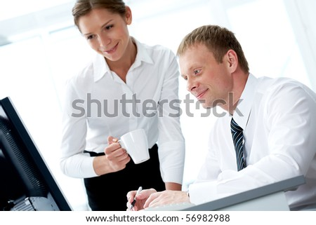 Successful businessman looking at monitor with his pretty colleague near by - stock photo