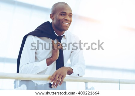 Successful businessman. Low Angle view of cheerful young African man in shirt and tie looking away and smiling - stock photo