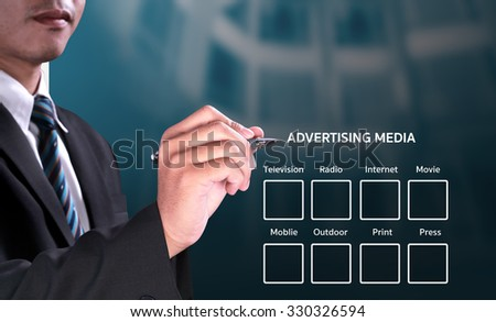 successful businessman making choices on advertising media quiz with magic pen on visual screen board over blue light modern office background - stock photo