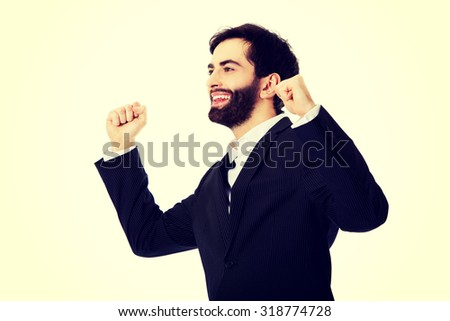 Successful businessman making fists in a winner gesture. - stock photo