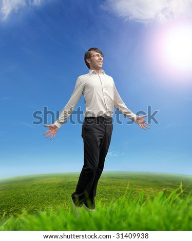 Successful businessman on a meadow - stock photo