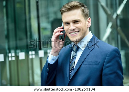 Successful businessman on the phone outside office building - stock photo