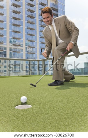 Successful businessman  or man in a suit playing golf on a corporate putting green on roof of a skyscraper office building - stock photo