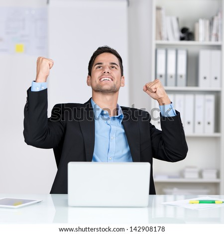 Successful businessman rejoicing raising his face to the sky and punching the air with his fists as he sits at his desk in the office
