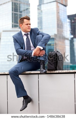 successful businessman resting on a background of office buildings