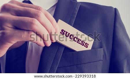 Successful businessman showing a wooden card reading - Success - as he withdraws it from the pocket of his suit jacket, close up of his hand with retro faded filter effect. - stock photo