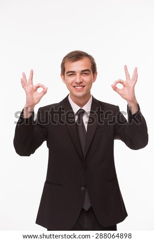 Successful businessman showing OK signs in his business world. Man in fashionable business suit smiling for camera.