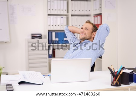 Successful businessman sitting daydreaming at the office with a pleased smile sitting relaxing in his chair with his hands clasped behind his head