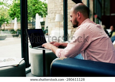 Successful businessman sitting front open laptop computer with blank screen for your content, young freelancer work on notebook in modern coffee shop or hotel interior, make money on-line, e-business - stock photo