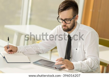 Successful businessman sitting in an office and writing some notes in his planner