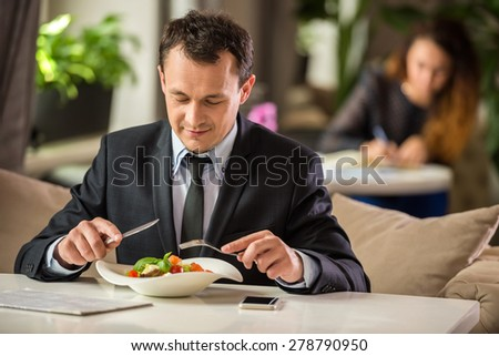 Successful businessman sitting in cafe and eating salad. - stock photo