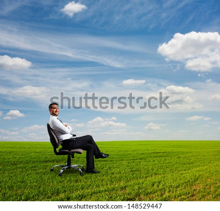 successful businessman sitting on field and resting