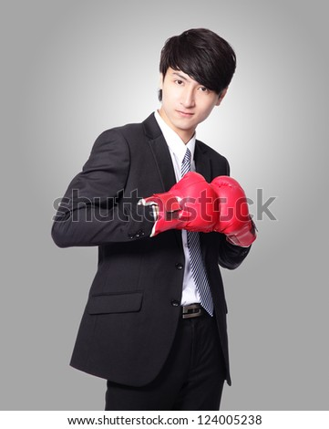 successful businessman smile with boxing gloves isolated on gray background,  Business competition concept, asian model - stock photo