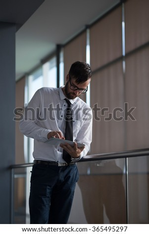 Successful businessman standing in an office building, holding a tablet computer, preparing for a meeting