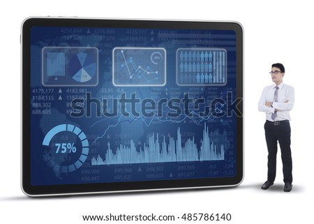 Successful businessman standing next to financial statistics on the futuristic screen, isolated on white background