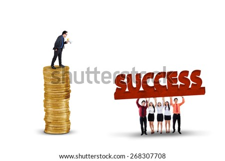 Successful businessman standing on the golden coins while giving orders his workers to lift a success text - stock photo