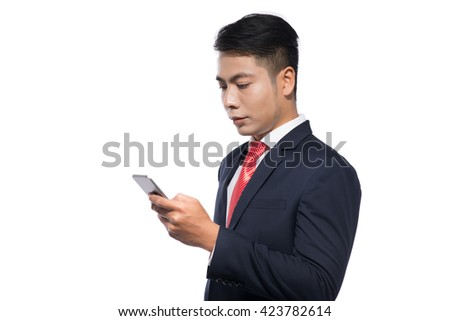 Successful businessman standing using smartphone access the internet as he leans against white with copyspace - stock photo