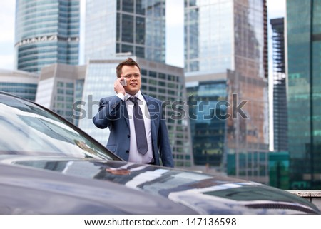 successful businessman talking on the phone near the car, on the background of office buildings - stock photo