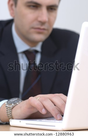 Successful businessman typing on his white computer