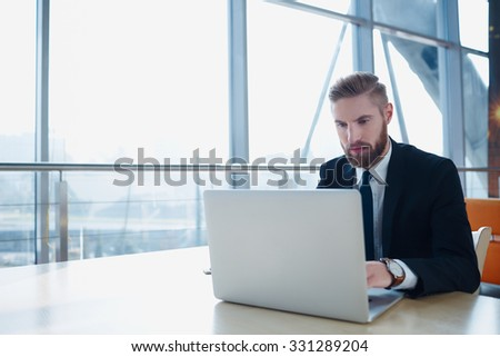 Successful businessman typing on laptop at modern office - stock photo
