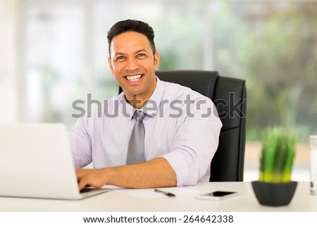 successful businessman using laptop computer in office - stock photo