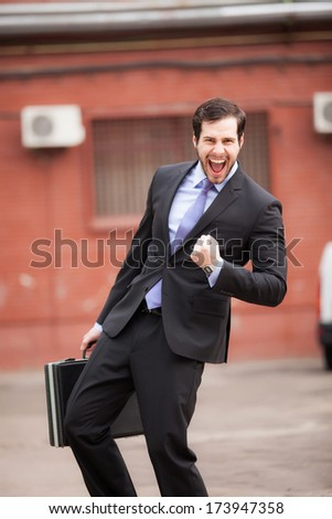 successful businessman very happy on the street - stock photo