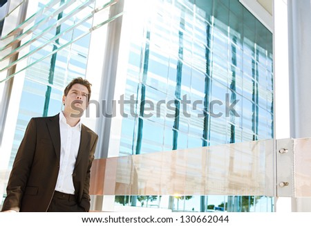 Successful businessman walking by a modern glass office building in the financial district city on a sunny day, outdoors. - stock photo