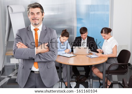 Successful Businessman With Arm Crossed Standing In Front Of His Colleagues