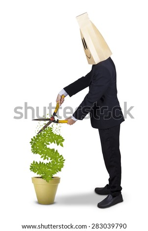 Successful businessman with cardboard head cutting money tree with a scissors - stock photo