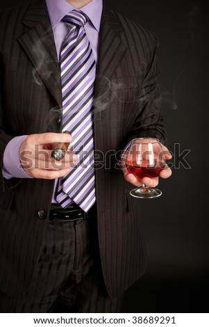Successful businessman with glass of cognac and good cigar over black