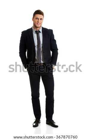 Successful businessman with hands in pockets. - stock photo