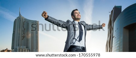 Successful businessman with his arms wide open. Joyous man  with success perspective, modern buildings at background - stock photo