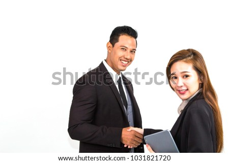 Successful businessman with suit and tie shaking with his beautiful partnership in modern office.