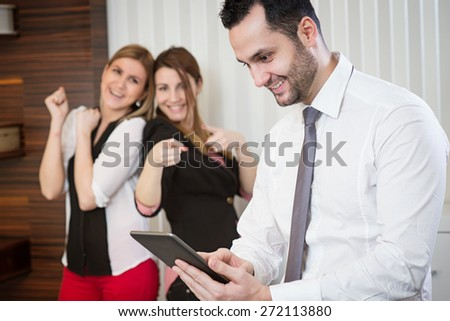 Successful businessman with tablet at office. Two female colleague rejoice in background. - stock photo