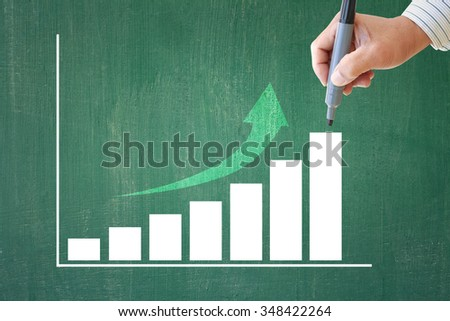 successful businessman writing summary of year achievement bar chart - stock photo